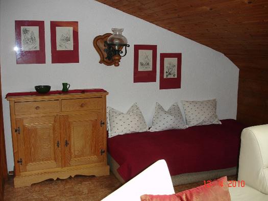 Wohnbereich mit Vollholz-Kommode, großer Couch mit Polster, Wandlampe, Bilder. (© Familie Laireiter)