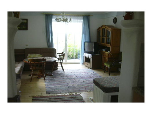 Wohnbereich mit Eckbank, Tisch und Stühle, im Hintergrund Balkontür, Fernseher, Kommode. (© Handl)
