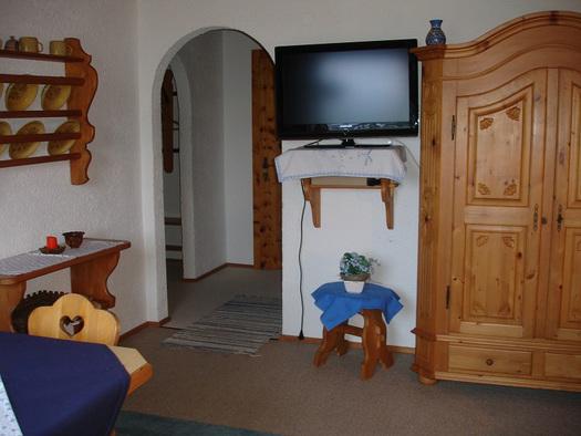 Wohnbereich mit Fernseher, Vollholz-Schrank, seitlich ein kleiner Teil vom Tisch und Stuhl. (© Familie Laireiter)