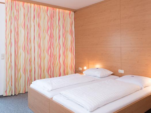 Zimmer mit Doppelbett, Nachttisch mit Lampe, Balkontür mit Zugang zum Balkon und Vorhang. (© Hotel Prielbauer)