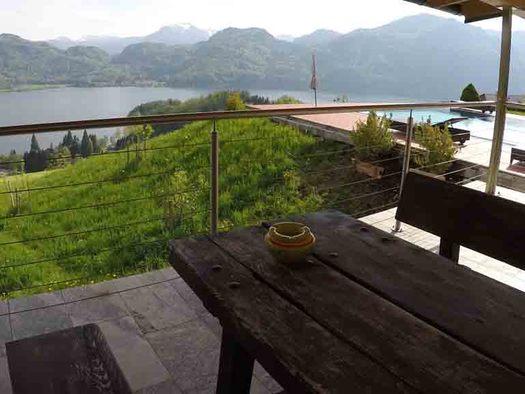 Terrasse mit Tisch und Bänke, seitlich der Pool, im Hintergrund der See und die Berge. (© Wiener)