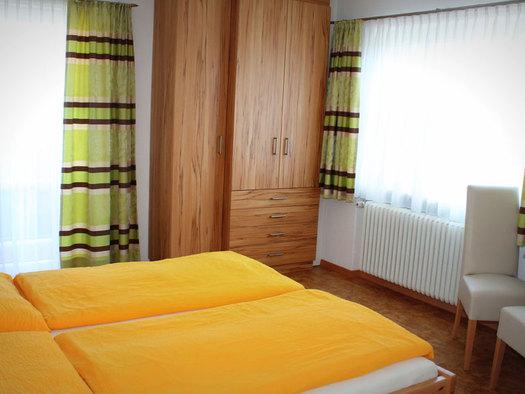 Doppelbett, seitlich ein Kleiderschrank, Balkontür, im Hintergrund ein Fenster, Tisch mit Stühle. (© Winter)