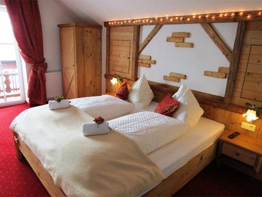 Schlafzimmer mit Doppelbett, Rosen auf dem Bett, Nachtkästchen, Lampen, seitlich eine Balkontür und Kleiderschrank. (© Stabauer)