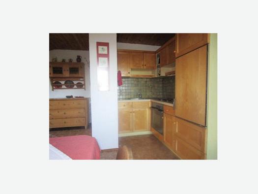 Wohnbereich, seitlich eine Küche, Herd, Vollholzmöbel. (© Familie Laireiter)