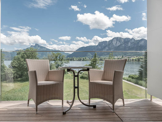 Terrace with table and chairs, view of the countryside, the lake and the mountains. (© Lackner)