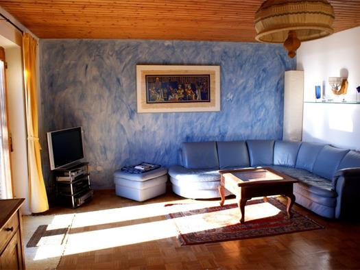 Wohnbereich mit großer Couch, kleiner Hocker, Tisch, TV und ein Bild an der Wand. (© Riess)