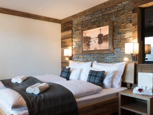Hotelzimmer im urig-modernen Stil, mit Doppelbett und Nachtkästchen. (© www.mondsee.at)