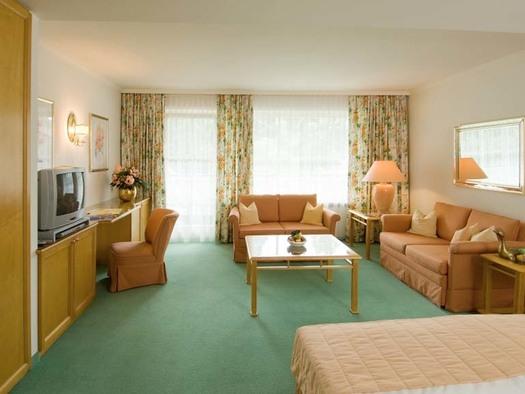 Im Vordergrund ein Teil vom Tett, dahinter Tisch und Sofas, seitlich Fernseher und Stühl, im Hintergrund Fenster und Balkontüre, Teppichboden. (© Hotel Seehof)