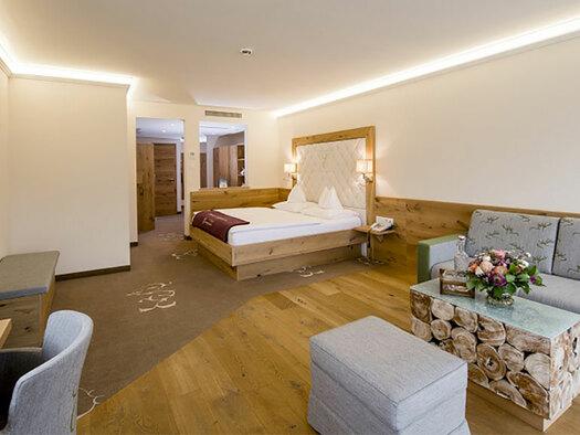 links Fernsehehr und Schreibtisch, rechts, Hocker, Tisch und Couch, im Hintergrund Doppelbett. (© Karin Lohberger)