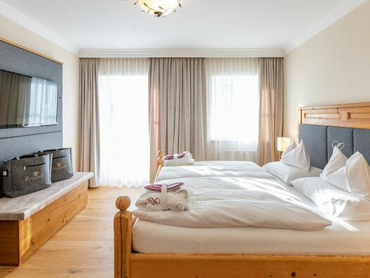 Großes Holzdoppelbett, TV an der Wand, darunter Sitzbank mit 2 grauen Taschen darauf. (© Eichingerbauer)