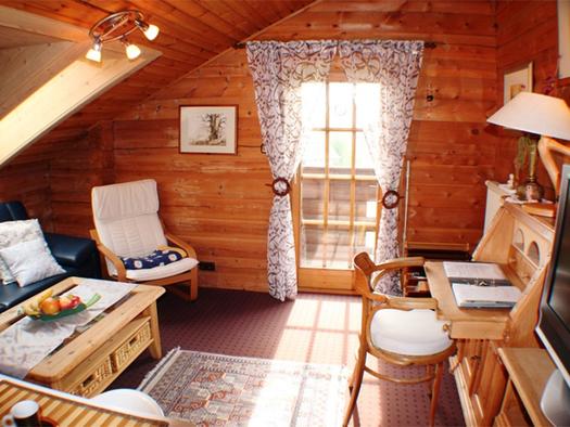 Wohnbereich mit Vollholzmöbel, Couch und Sessel, im Hintergrund eine Balkontür. (© Schorn)