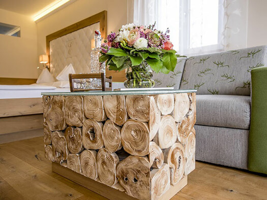 Wooden table with flowers and couch, in the background the double bed, wooden floor. (© Karin Lohberger)