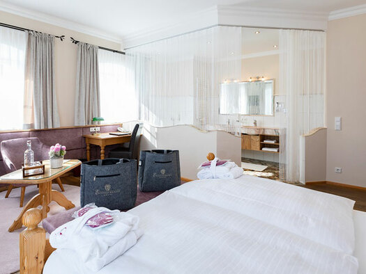 View from the bed to the half-open bathroom, desk with reading lamp, 2 chairs with a small table, bottle and flowers on it, 2 gray pockets in front of the bed. (© Eichingerbauer)