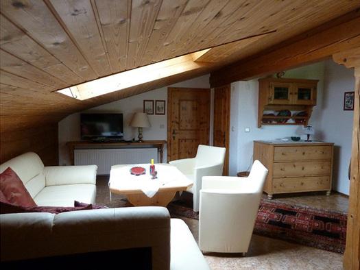 Wohnbereich, mit Couch und Tisch, im Hintergrund Kommode, Fernseher, Tischlampe. (© Familie Laireiter)