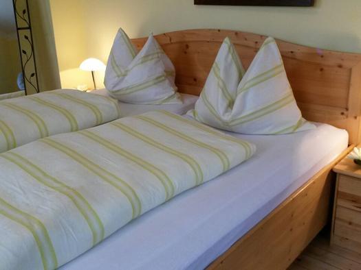 Schlafzimmer mit Doppelbett, Nachtkästchen mit Lampe. (© Daxinger)