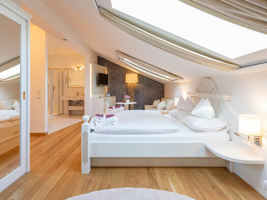 Bed with reading lamps, view of the bathroom, TV on the wall, standard lamp, large mirror. (© Eichingerbauer)