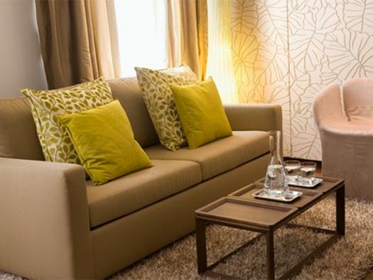 Suite mit Sofa und Polstern, Sessel, Tisch mit Wasserkaraffe und Gläser. (© Hotel Iris Porsche)