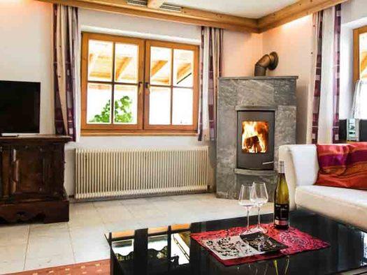 Wohnbereich, seitlich eine Couch, Tisch mit Gläser und Flasche, im Hintergrund Kamin, Fenster, Kommode, Fernseher. (© Wiener)