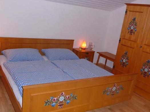 Schlafzimmer mit Doppelbett, Nachtkästchen und Kleiderschrank. (© Gästehaus Horizont)