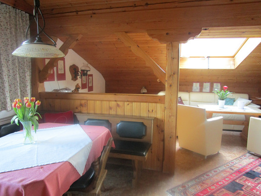 Wohnbereich mit Eckbank, Tisch, Stühle, Vase mit Blumen, im Hintergrund Couch mit Tisch, Stühle, Dachfenster. (© Familie Laireiter)