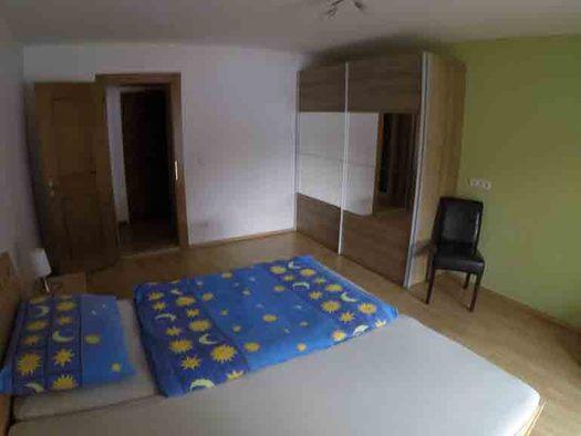 Schlafzimmer mit Doppelbett, im Hintergrund offene Tür, Kleiderschrank, Sessel. (© Wiener)