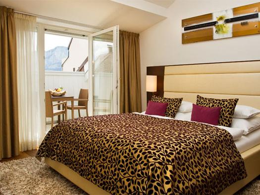Schlafzimmer mit Doppelbett, Blick auf den Balkon mit Tisch und Stühlen. (© Hotel Iris Porsche)