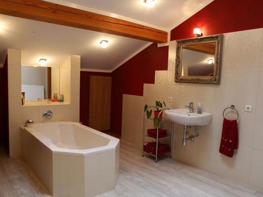 Badezimmer mit Wanne, Waschbecken, Spiegel. (© Familie Radauer)
