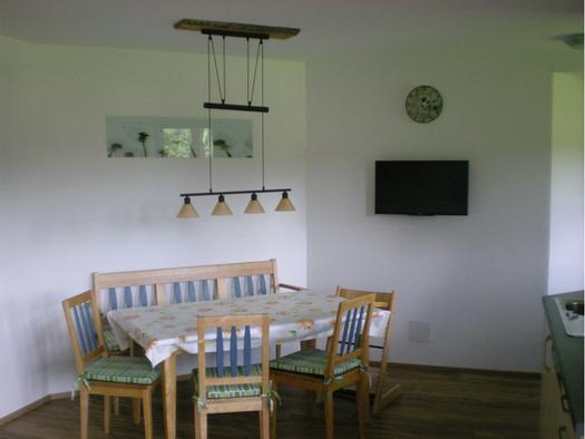 Essecke mit Bank, Tisch, 3 Stühlen und Kindersessel, Hängelampe, Fernseher im Hintergrund. (© Mayrhofer)