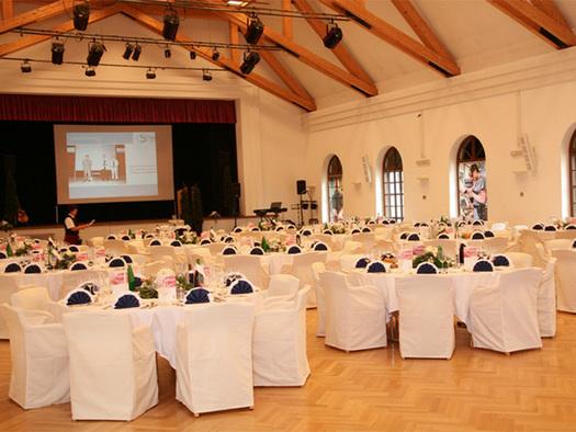 Festsaal - festlich gedeckte Tische, Stühle mit Hussen, im Vordergrund die Bühne mit einer Leinwand. (© Schloss Mondsee)