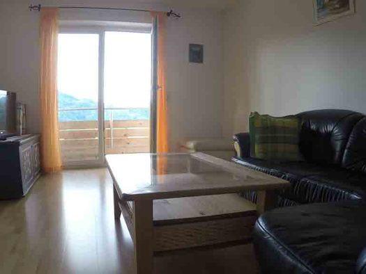 Wohnbereich, seitlich eine Ledercouch, Tisch, im Hintergrund eine Kommode mit Fernseher, im Hintergrund Balkontür. (© Wiener)