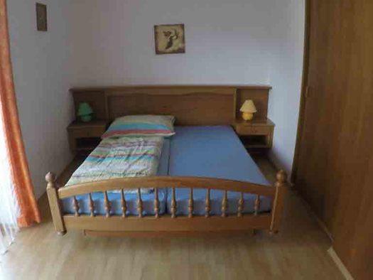 Schlafzimmer mit Doppelbett, Nachtkästchen, Tischlampen, seitlich eine Balkontür. (© Wiener)