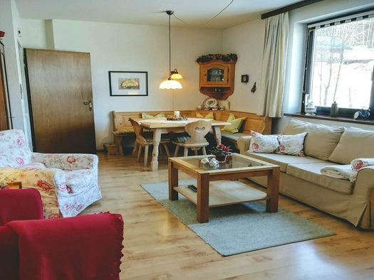 Gemütlicher Wohnraum mit rustikaler Eckbank und Tisch, Couch mit Couchtisch und zwei weiteren Sitzmöglichkeiten. (© Adelheid Haböck)