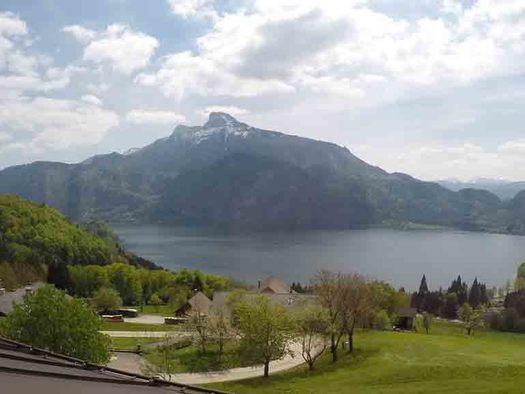 Ausblick auf die Landschaft, mit Wiesen, Bäume, im Hintergrund See und Berge. (© Wiener)