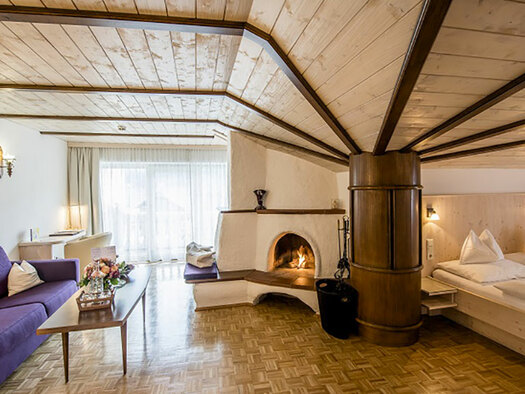 left couch, in the middle chimney and right doublebed, wooden ceiling. (© Karin Lohberger)