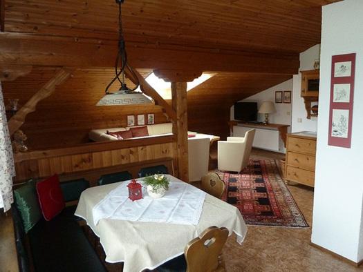 Wohnbereich mit Eckbank, Tisch und Stühle, im Hintergrund Couch, Sesseln, Kommode. (© Familie Laireiter)