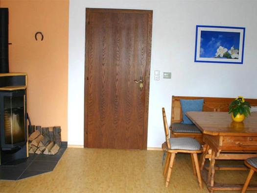 Wohnbereich mit Kachelofen, Tisch und Stühle. (© Gästehaus Horizont)