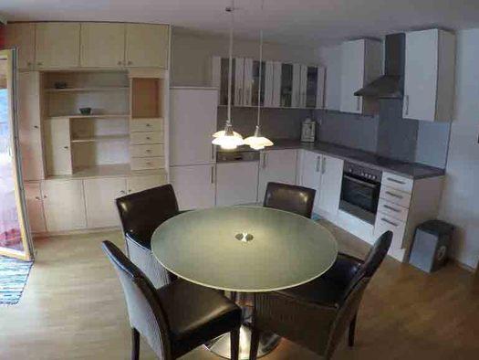 Wohnbereich, Tisch mit Stühlen, im Hintergrund Küche mit Geschirrspüler, Kaffeemaschine, Herd, seitlich eine Balkontür. (© Wiener)