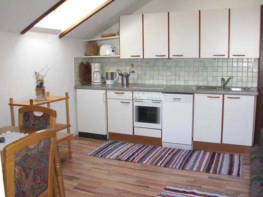 Blick in die Küche mit Kaffeemaschine, Wasserkocher, Herd, Geschirrspüler, Spüle, im Vordergrund ein Tisch und Stühle. (© Winter)