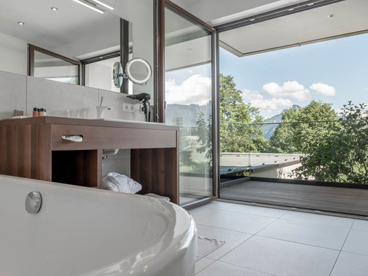 Bathtub, bathroom furniture on the side, view through the open terrace door to the countryside. (© Lackner)