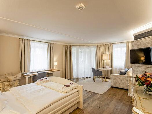 Helles Zimmer mit Holzboden, im Vordergrund das Doppelbett, im Hitergrund ein Schreibtisch, ein Tischchen mit Leselampe, Balkontüren, Couch, Flatscreen, rechts im Vordergrund eine Spiegeltischchen mit Blumen. (© Karin Lohberger)