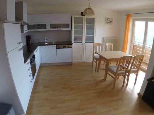 Küche mit Herd, Kaffeemaschine, Spüle, Geschirrspüler, Tisch mit Stühlen, seitlich Balkontür. (© Wiener)