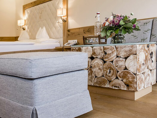 Hocker mit Tisch mit Blumenstrauße und Couch, im Hintergrund das Doppelbett. (© Karin Lohberger)