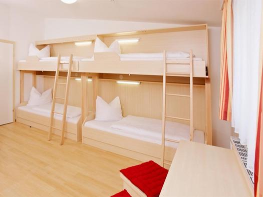 Zimmer mit einzelnen Stockbetten, Leiter, seitliche ein länglicher Tisch mit Hocker, Fenster. (© Jugendgästehaus)