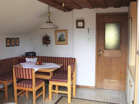 Essbereich mit Eckbank, Tisch, im Hintergrund ein Radio, Bilder an der Wand. (© Edtmayer)