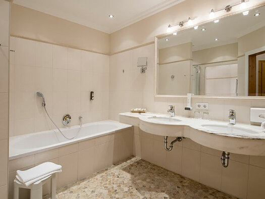 right two lavatories and a big mirror, left bathtub and shower. (© Karin Lohberger)