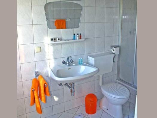 Blick ins Badezimmer mit Waschbecken, Spiegel und Toilette. (© Gästehaus Horizont)
