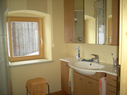 Ein Badezimmer mit Dusche und Bick auf den Hof