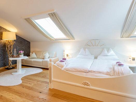 Doppelbett mit Leselampen, Couch mit kleinem Tisch mit Flasche und Blumen drauf, Teppiche auf Holzboden, Stehlampe und TV an der Wand. (© Eichingerbauer)