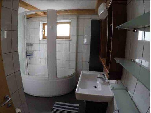 Badezimmer mit Dusche, Waschbecken, Ablageregale, im Hintergrund ein Fenster. (© Wiener)