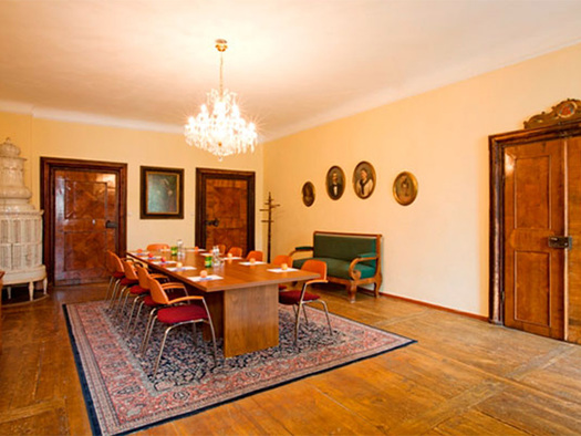 alter Holzboden, Tisch mit Stühle, Teppich, Couch, alter Kachelofen im Hintergrund. (© Schloss Mondsee)